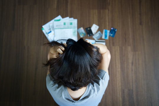 Top view of stressed young Asian woman hands holding the head trying to find money to pay credit card debt and all loan bills. Financial problem concept.
