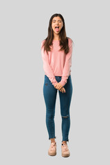 Full body of Teenager girl with pink shirt showing tongue at the camera having funny look on isolated grey background