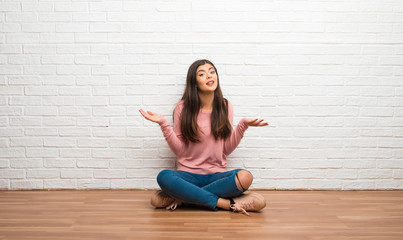 Teenager girl sitting on the floor in a room having doubts while raising hands and shoulders