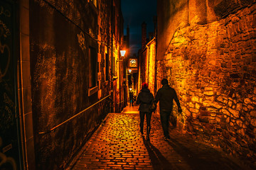Couple walking through a narrow street in Edinburgh at the Royal Mile night shot Edinburgh at Night...