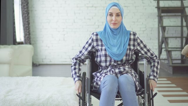 beautiful young woman in hijab disabled person, wheelchair, in apartment