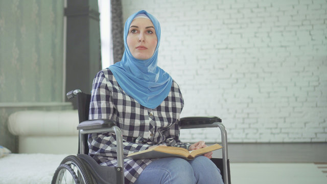 A beautiful young woman in a hijab is blind or weakly imposing, a wheelchair reading a braille font.