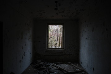 Urbex, scary abandoned and dark room with broken window
