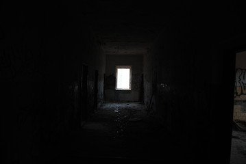 Dark corridor of abandoned decay building with light at the end, urbex