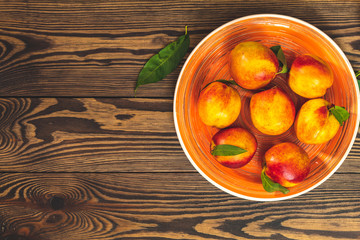 Peaches in orange plate on dark wooden background