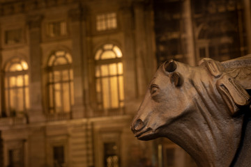 Turin, Piedmont, Italy: night view of bull head detail in the basement of a street lamp with in background Palazzo Madama in Piazza Castello.
