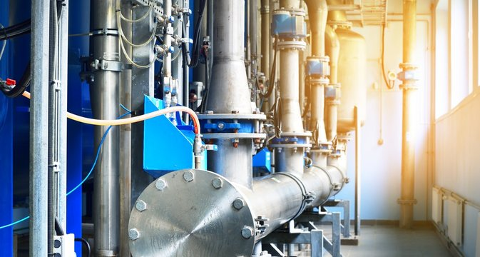 Large industrial water treatment and boiler room. Piping, flanges, butterfly valves