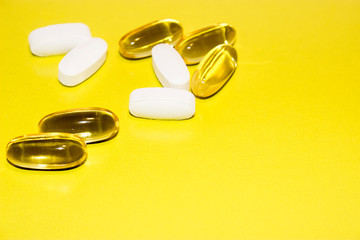 colorful medical pills, on yellow background, closeup