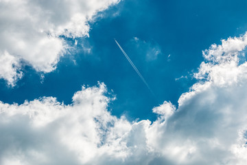 A plane above the clouds in the deep blue sky