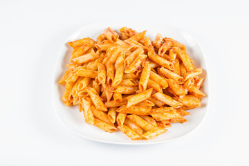 Penne with pesto on a plate on a white background