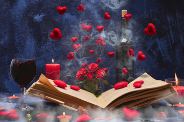Valentine day. Book in the smoke with flying hearts. Book, hearts, candles, fog, smoke, flowers, wine on a blue background. Magic for lovers. Splash of red wine. A wonderful romantic evening . Love.
