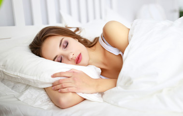 beautiful young woman sleeping in bed in the morning