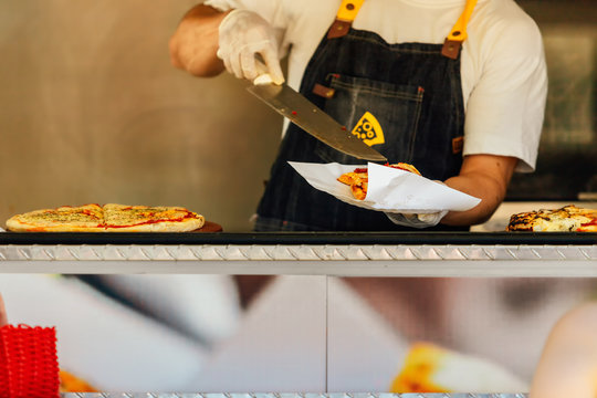 Pizza man serving pizza on a napkin in a food truck