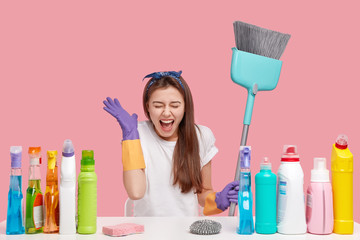 Photo of overjoyed brunette woman keeps hand near face, exclaims and laugh happily, wears headband, rubber gloves, carries broom for sweeping floor, sits against pink background. Time for cleaning