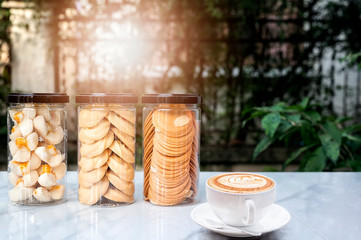 Cookies in a black cover bottle and cup of coffee on white table with nature background.