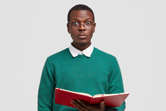 Photo of surprised black male teacher looks directly at camera, wears spectacles, carries notepad with notes, conducts lecture, dressed in casual clothing, models over white background. Serious reader