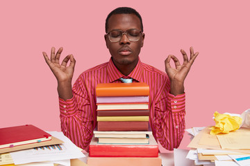 Black relaxed young male manager practices yoga at work place, takes rest for wellness, avoids stress, makes okay gesture with both hands, surrounded with books and papers. Mental health concept