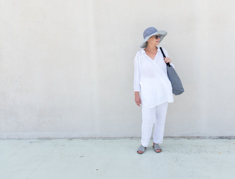Full length view of beautiful senior woman in grey hat and light white summer clothing against wall (selective focus)