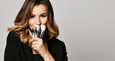 Beauty woman hold makeup professional tools mascara eyelashes brushes have clear healthy face portrait Wall mural