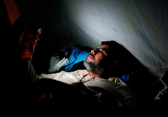 Oscar Henry Rojas lies in his tent while on a hunger strike to protest against Bolivia's President Evo Morales' bid for re-election in 2019, in La Paz