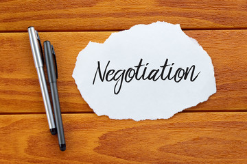 Business and finance concept. Top view of pen and piece of paper written with negotiation on wooden background,