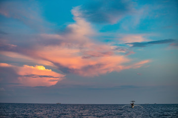Beautiful sunrise clouds and sky with indonesian fisherman boat on water surface background