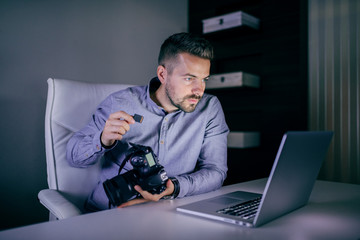 Serious photographer looking at laptop and putting memory card in camera while sitting late at night in studio.