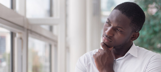 serious african business man thinking or planning; portrait of thoughtful black man thinking, planning, considering, finding a good idea; young adult african man model
