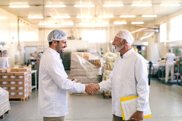 Two happy coworkers shaking hands while standing in the food factory.