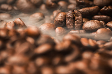 Close up pile of Coffee beans roasting with smoke