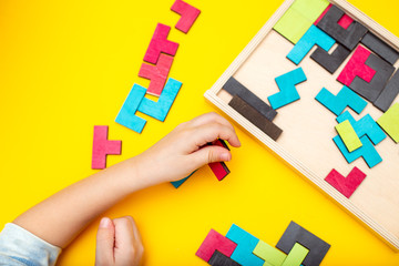 Wooden puzzle and kids hands on yellow background. Flat lay