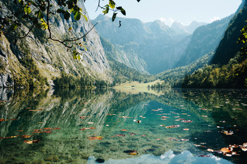 Lake Obersee in scenic National park Berchtesgadener. Beautiful teal blue water of Lake Obersee covered by leaves in sunny autumn day, Bavaria, Germany.