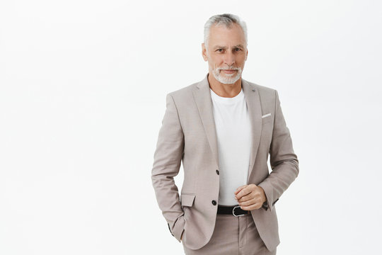 Finance, business and success concept. Portrait of rich senior male entrepreneur in elegant suit with grey hair and beard checking outfit and smiling delighted at camera attending party with investors