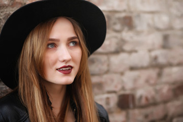 A girl walks down the city street in a leather waistcoat with a phone. Young beautiful girl in a hat and with a dark make-up outside. Girl in the Gothic style on street.
