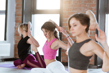 Group of sporty women in fitness studio practice yoga Kapotasana or Pigeon pose variations. Healthy lifestyle and wellness, recreation concept
