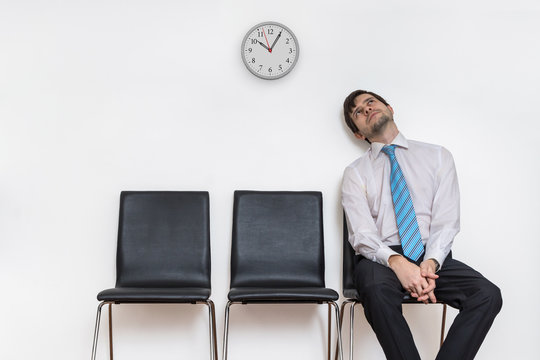 Tired and exhausted man is sitting in waiting room on chair.