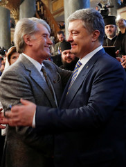 Ukrainian President Petro Poroshenko hugs Former Ukrainian President Viktor Yushchenko after the Epiphany mass at the Patriarchal Cathedral of St. George in Istanbul