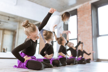 The choreographer teaches children to dance. Kids dance class in loft studio with windows and sunlight