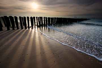 sunshine over old wooden breakwater on North sea coast Wall mural