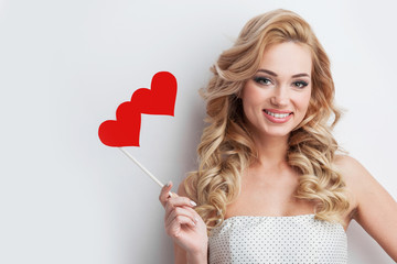 Positive girl holds red hearts