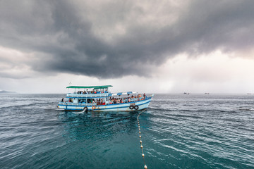 Traveling boat with passenger go to island while raining strom near comes