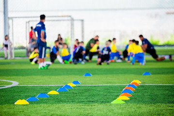 Cone markers is soccer training equipment on green artificial turf with blurry kid players training background