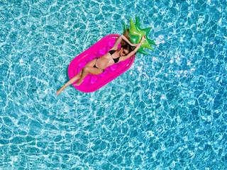Sportliche, junge Frau im Bikini entspannt auf einer Luftmatratze im Pool an einem heißem Sommertag