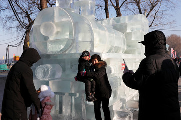 People pose next to an ice sculpture during annual ice festival, in the northern city of Harbin, Heilongjiang province