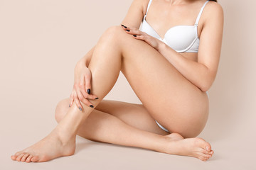 Cropped shot of half naked young woman wears white lingerie, shows slender legs, has healthy smooth skin, crossed legs, sits on floor against beige background, has perfect figure, poses bare foot.
