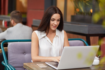 Pleased brunette woman in white clothes sits in front of opened laptop, reads response, recieves email on gadget, works as journalist, poses at desk in outdoor cafeteria connected to wireless internet