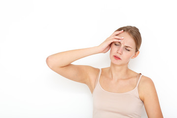 Portrait of a young European woman with blond hair. She has a headache and she has put her hand to her head.