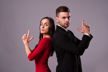 Beautiful stylish and elegant couple in suit and dress are standing back to back, have a fun and posing isolated in studio. Holidays and events. St Valentine's day. Day of lovers
