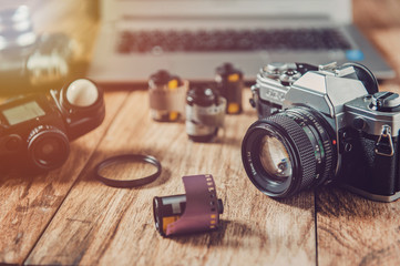 Analog camera, film rolls and vintage photography accessories along with modern equipment and laptop.
