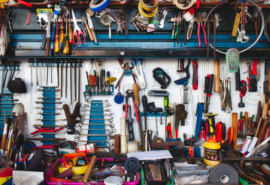 A collection of assorted tools hanging on the wall with a work bench in a garage